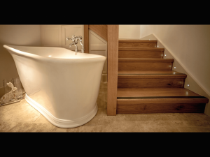 Wooden Staircase leading into bathroom with tiled floor