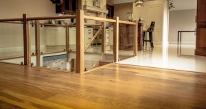 Room divided by wood flooring and tiles in kitchen.