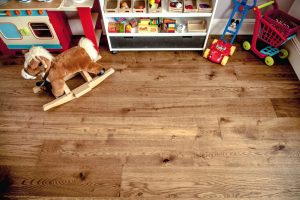 Beautiful wood flooring with childrens toys along a wall.