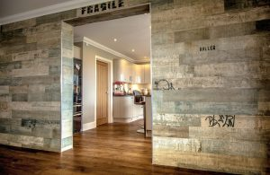 Wooden flooring next to industrial style wall with reclaimed wood.