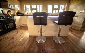 Wooden Floor in a kitchen. Two stool chairs sit at an island in front of the camera