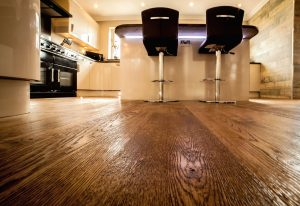 Wooden Floor in a kitchen. Two stool chairs sit at an island in front of the camera - low angle