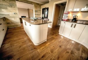 Beautiful kitchen wood flooring, island and reclaimed wooden wall.