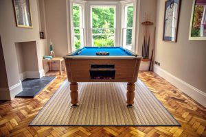 Pool Table on a rug over zigzagged wooden flooring