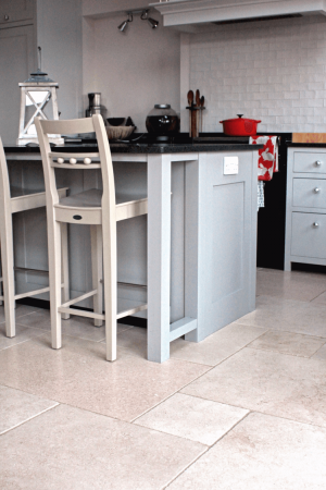 Tiled kitchen with grey cupboards and tall chairs.