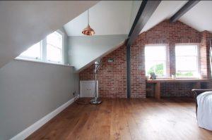 Spacious Attic, hardwood flooring again large red brick wall