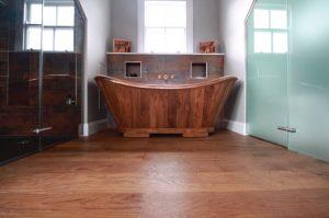 Copper bath on brown red wood flooring