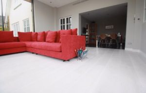 Hard Wood Flooring, Red Sofa with magazine rack next to it
