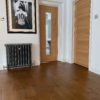 Barnston Mixed Width Traditional Oil Oak Flooring installed in Living Room with Cast Iron Radiator